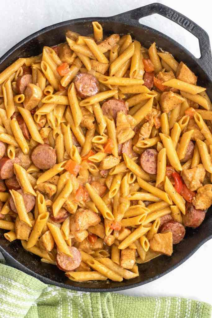 How to make a quick cajun chicken and sausage pasta dinner in one skillet in under 30 minutes. Perfect for a high protein meal prep or a weeknight dinner for the family.