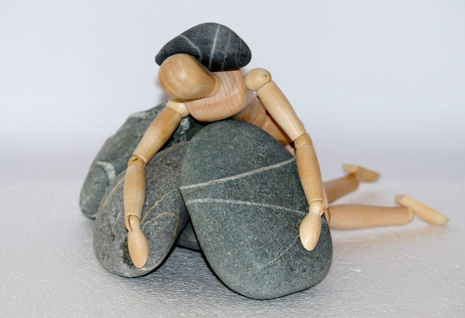 Wooden doll stuck under pile of rocks