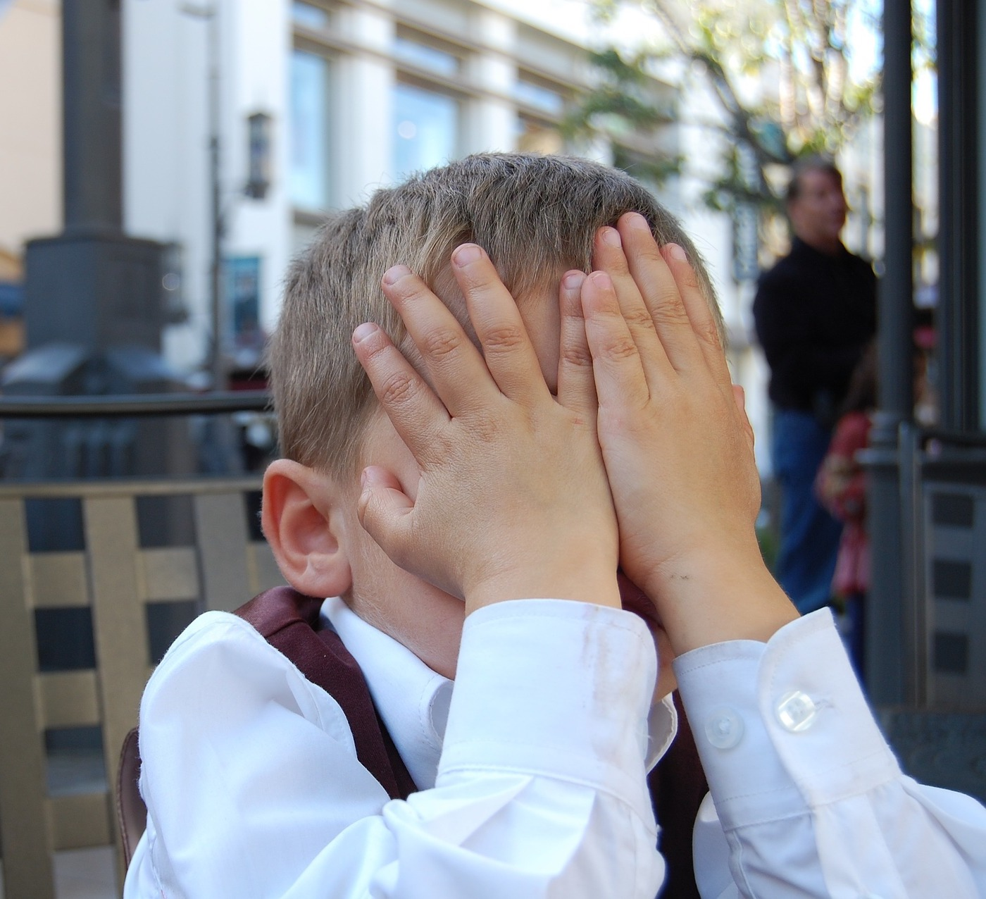 Young boy covering his face in shame