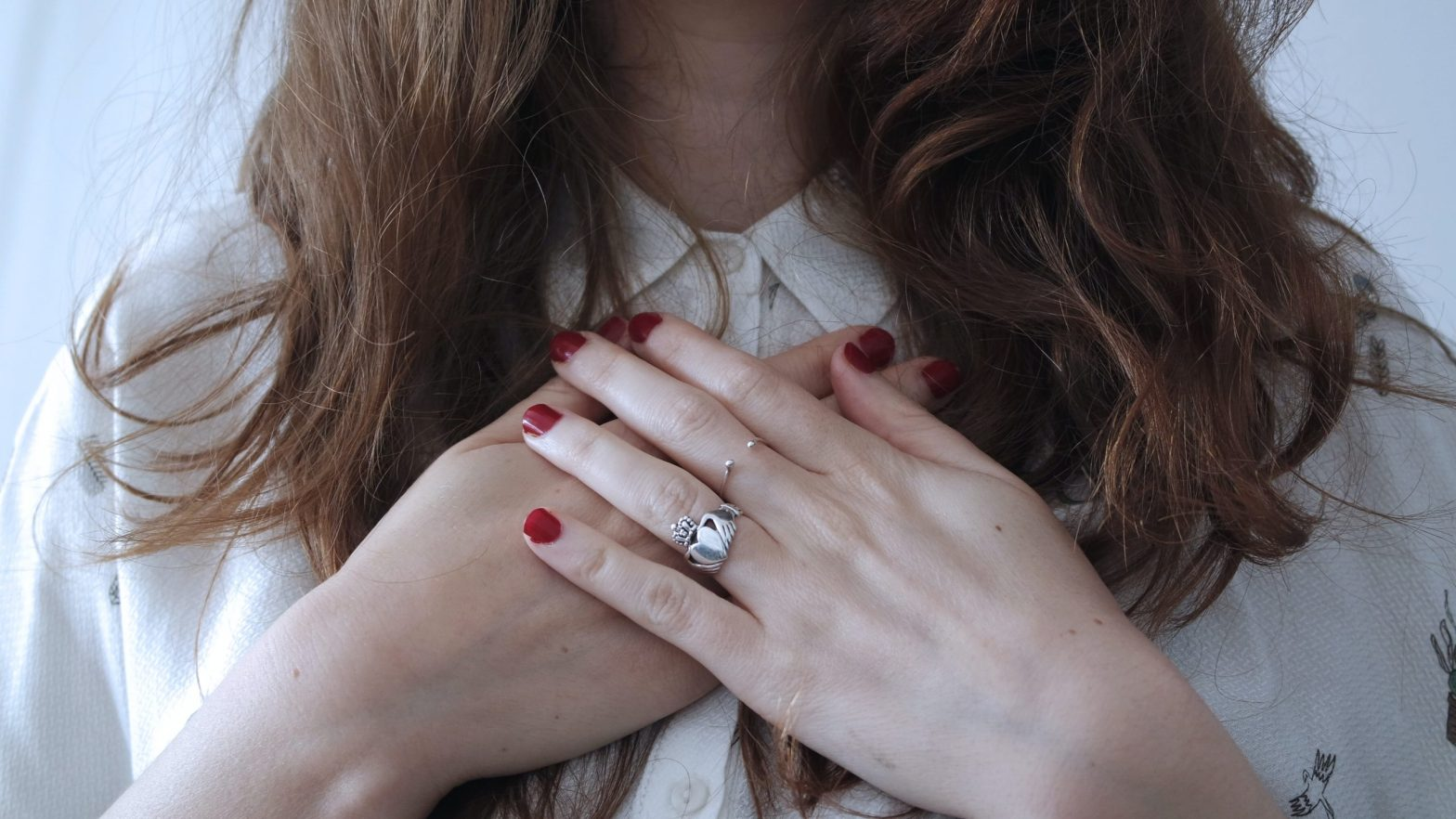 Woman with hands over her heart, demonstrating self-love