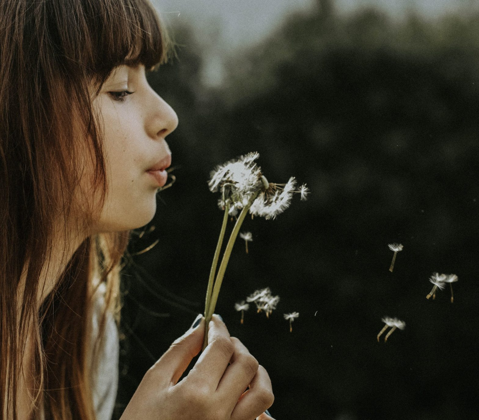 Woman blowing a dandelion, wishing to attract a healthy partner