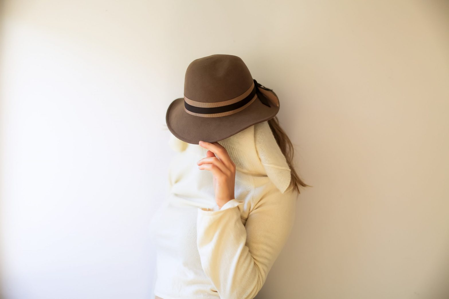Woman with a hat on and something covering her face: vulnerability avoidance tactics