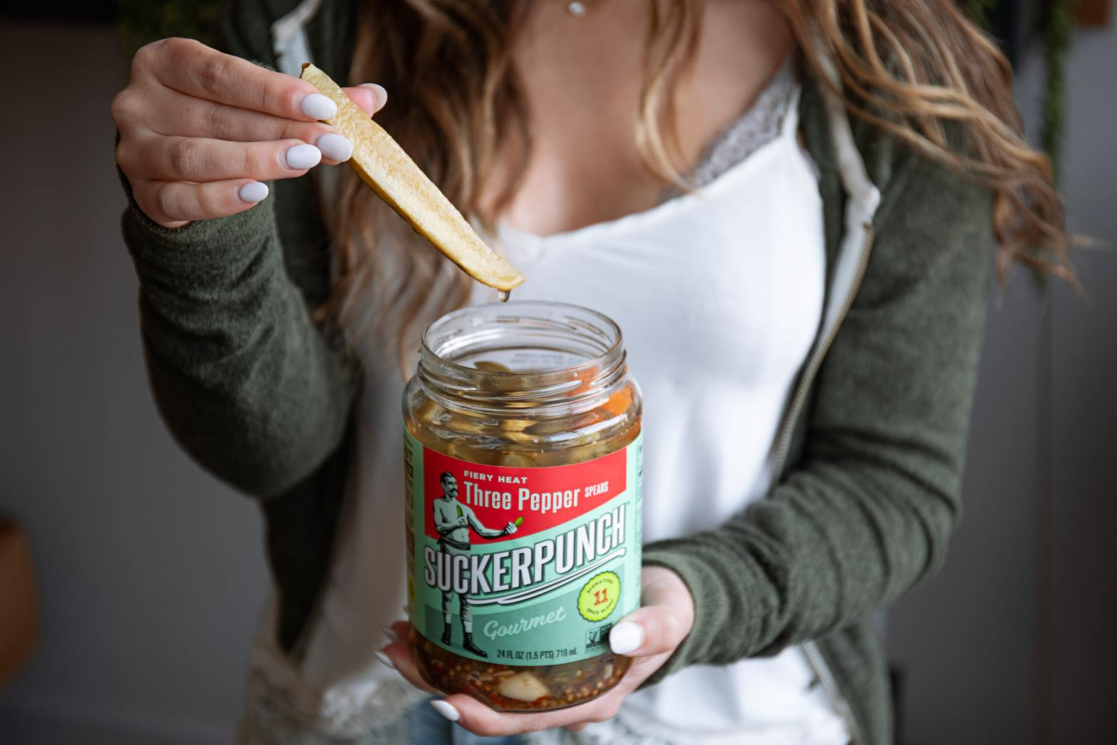 Woman holding an open jar of pickles in one hand and a pickle in the other –Pickels Can't Read Their Own Label