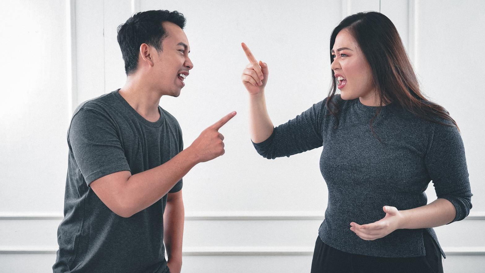 Couple arguing and pointing at each other –conflict in relationships.