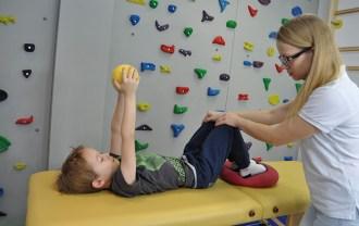 chłopiec wykonujący ćwiczenia fizjoterapetyczne w wykorzystaniem piłki