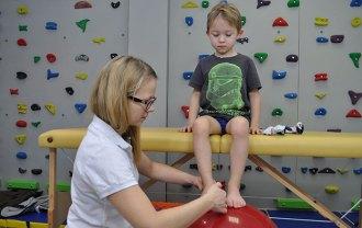 ćwiczenia fizjoterapeutyczne chłopca na czerwonej piłce