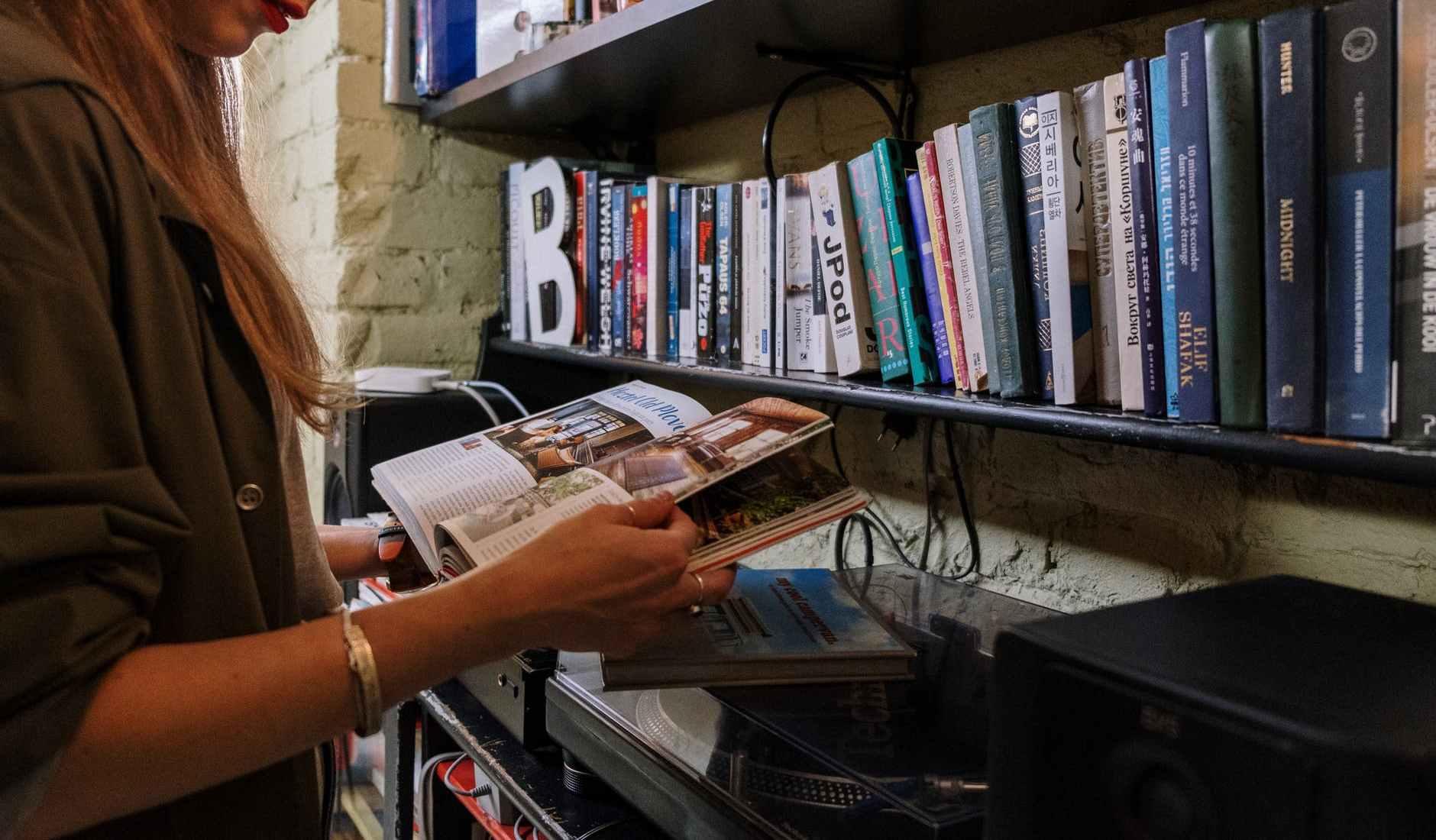 woman in white shirt holding magazine