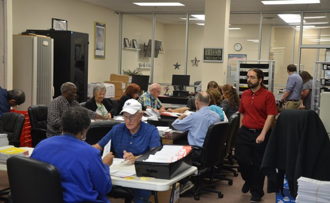 The Flagler Canvassing Board and election workers going through the 7,000-some mailed-in ballots that arrived today. It's a mid-term election, but the turnout numbers seem more like those of a general election. (© FlaglerLive)