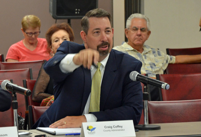 Don't blame him for being in the driver's seat: Most county commissioners have been incapable of giving County Administrator the clear direction he's sought on taxes in two successive budget hearings, so he's filling in the blanks. (© FlaglerLive)