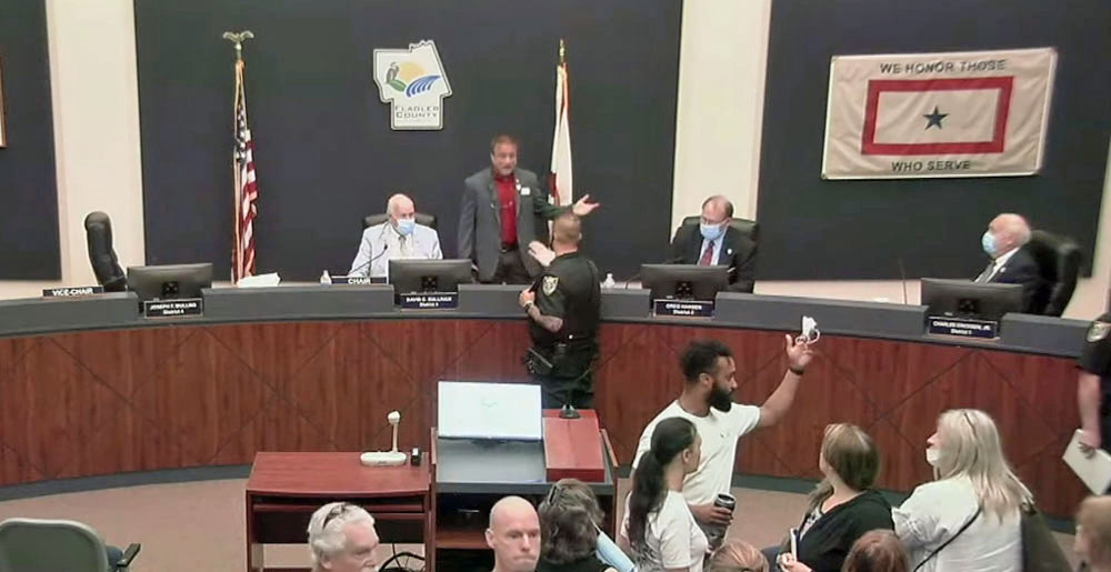 A flagler County Sheriff's deputy intervened as Commissioner Joe Mullins was insulting fellow-Commissioner Greg Hansen, to the right of Mullins on the dais, Wednesday during a commission meeting. Mullins later wanted to lodge a complaint against a deputy even as he spoke from the dais about the importance of supporting law enforcement. (© FlaglerLive via YouTube)
