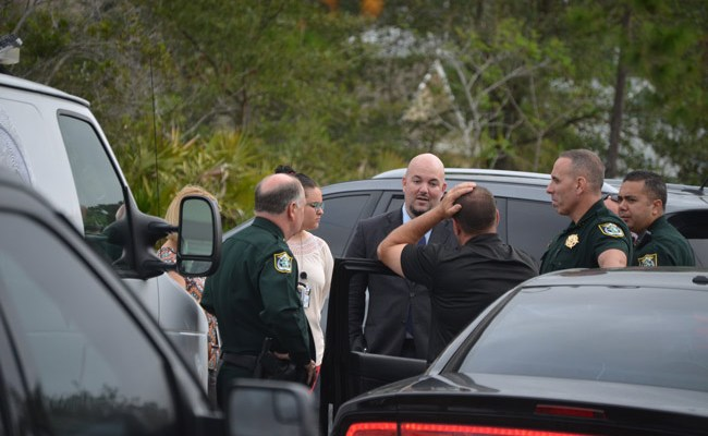 Flagler County Sheriff's detective George Hristakopoulos, center, with Sheriff Rick Staly, left, and other members of the sheriff's office outside of the Seamanship Trail house the morning of the shooting there that resulted in two young men being hospitalized, but no charges yet from that particular shooting. Evidence gathered from the scene, however, resulted in unrelated charges against one of the victims and suspects, Tristan George, now 19. (© FlaglerLive)