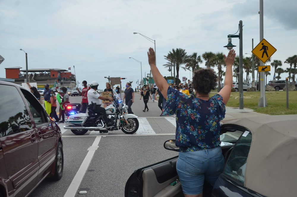"""A woman taking the """"don't shoot"""" stand in solidarity with marchers protesting police brutality in Flagler Beach last week. (© FlaglerLive)"""