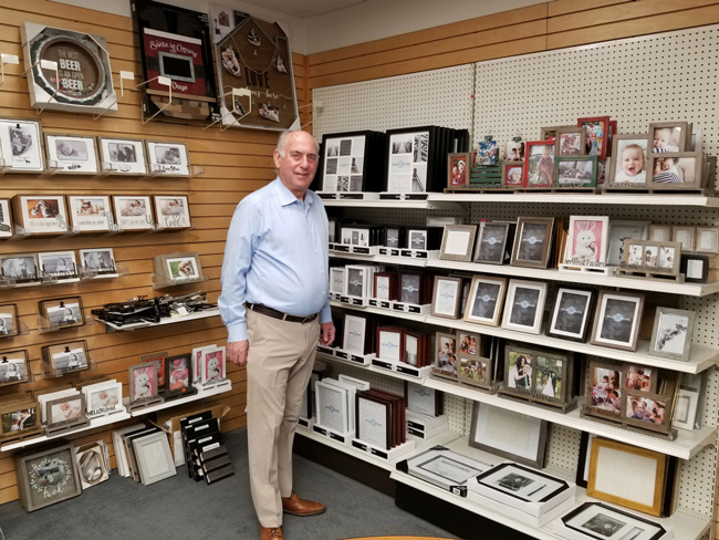 Richard Master, CEO of MCS Industries in Easton, Pa., stands in a showroom of the company's picture frames and wall decor. He says one of the biggest impediments to keeping labor costs in line has been the increasing expense of health coverage in the United States. (Phil Galewitz/KHN)