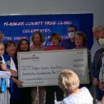 Tom Sisti of the AdventHealth Auxiliary gifting the Free Clinic the big check. (© FlaglerLive)