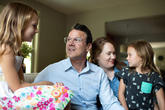 Drew Calver sits with his wife, Erin, and daughters Eleanor (left) and Emory (middle) in their Austin, Texas, home where he had a heart attack on April 2, 2017. Calver, a high school teacher, has health insurance through his school district, but still faced a $108,951.31 bill. (Callie Richmond for KHN)