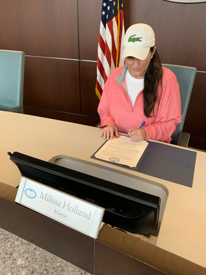 Mayor Milissa Holland signing a state of emergency proclamation earlier today. It was not sponsored by Lacoste. (Palm Coast)