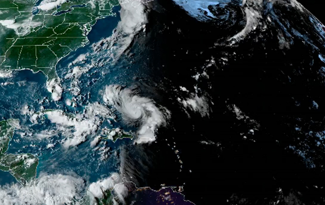 A satellite image of Hurricane Dorian approaching the Florida Peninsula as night falls behind it.