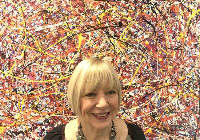 """Jan Jackson, curator of Grand Gallery, poses beside """"Vertigo,"""" a work by Dennis Mialki that is part of the current exhibit, """"Elements III, Part 2."""" (© FlaglerLive)"""