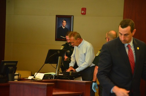 Assistant State Attorney Jason Lewis, in the foreground, who prosecuted the case, as David Zlokas is finger-printed in the background. (c FlaglerLive)