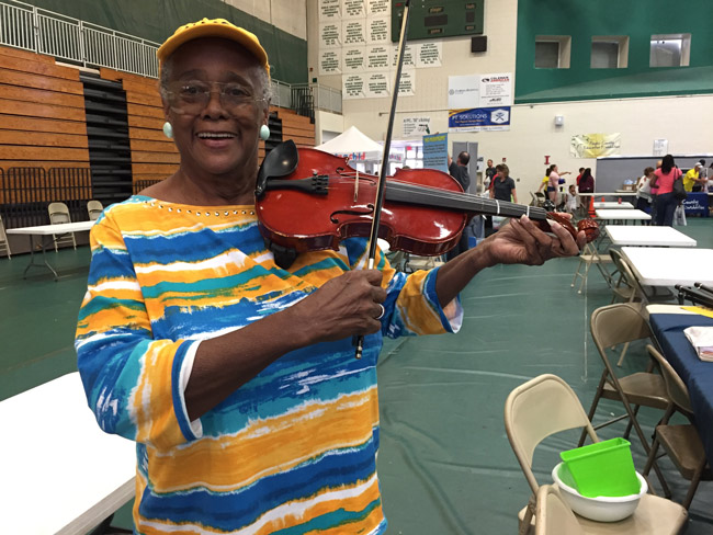 NAACP education advocate Jerusha Logan showed a few skills at Saturday's Back To School Jam at Flagler Palm Coast High School. The Jam drew an estimated 900 families, according to a school board member.  (© FlaglerLive)