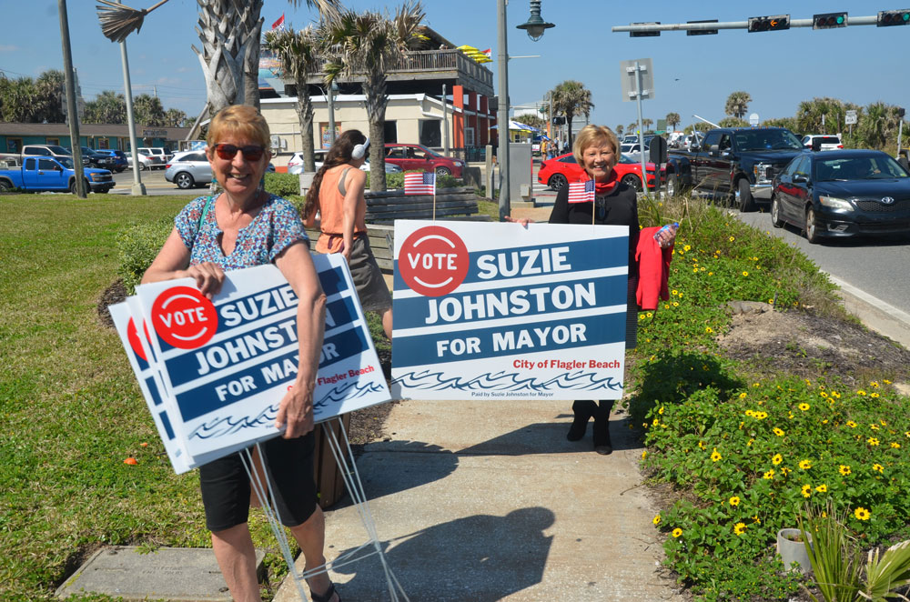 Flagler Beach's Carol Fisher, left, and Suzanne Johnston after a stint waving signs at the intersection of Old Moody Boulevard and State Road A1A on Saturday. (© FlaglerLive)