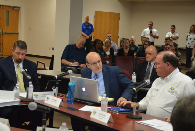 Dennis McDonald, second from left in the background, writing notes during a recent workshop on the Sheriff's Operations Center, with--at the table, from left--County Administrator Craig Coffey, County Attorney Al Hadeed, and County Commission Chairman Greg Hansen. (© FlaglerLive)