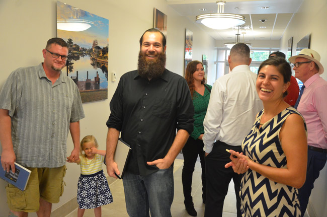 The Moonrise Brewing Company Crew after it won the unanimous approval of the Palm Coast Planning Board Wednesday. From left, Brewmaster Vance Tyson Joy and his nearly 3-year-old daughter Leia, parnters Benjamin Davenport and Ashley Dees (in the background), and, toward the right, European Village business owner Laura Castro, who is leasing the three units where the brewing company will operate. 'I'm planning on brewing the best beer of my life for this company,' Joy says. (© FlaglerLive)