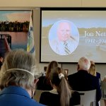 A memorial for former Palm Coast Mayor Jon Netts earlier this year sharpened the sense that the city was heading toward a fork in its direction, possibly a distance away from the direction Netts and his follower, Milissa Holland, at the podium, set. (© FlaglerLive)