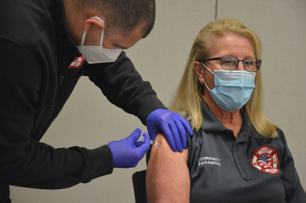 Caryn Prather, Flagler County Fire Rescue's Community Paramedic and one of the leaders of the county's 10-months-long Covid-testing program, getting her first dose of the Moderna vaccine on Tuesday at the Emergency Operations Center. She was one of about 20 people inoculated. (© FlaglerLive)