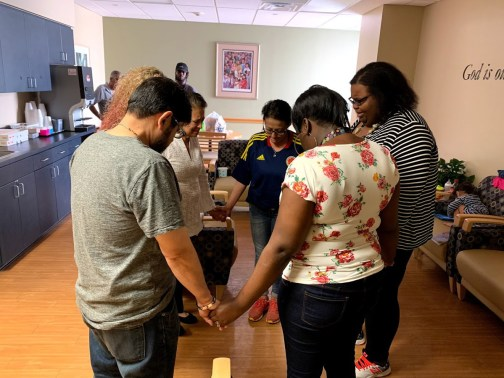 A moment of prayer in the ICU waiting room, with Anthony's mother, Erika Williams, and her mother, toward the center, and Anthony's uncle Carlos Trivino to the left. (© FlaglerLive)