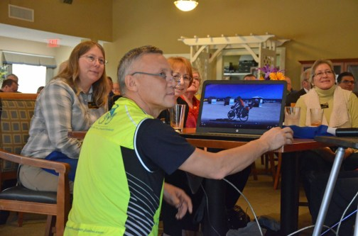Ildus Yanyshev showing various video clips from his trip at Tuesday's Rotary Club lunch, with Supervisor of Elections Kaiti Lenhart to his left, and club member Thea Mathen to his right. (© FlaglerLive)