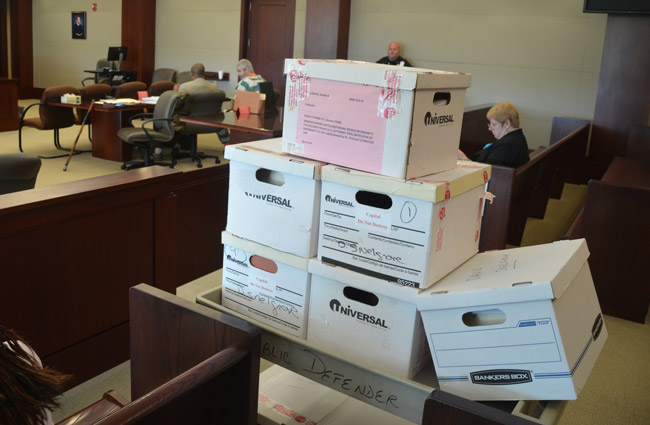 Some of the 20-odd boxes in David Snelgrove's murder case, brought in when he was last in court in 2015. He is seen in the striped green and white overalls in the distance. He was not in court today, but is scheduled to be in court in October for the next phase of his case, which has meandered through court since 2000. (© FlaglerLive)