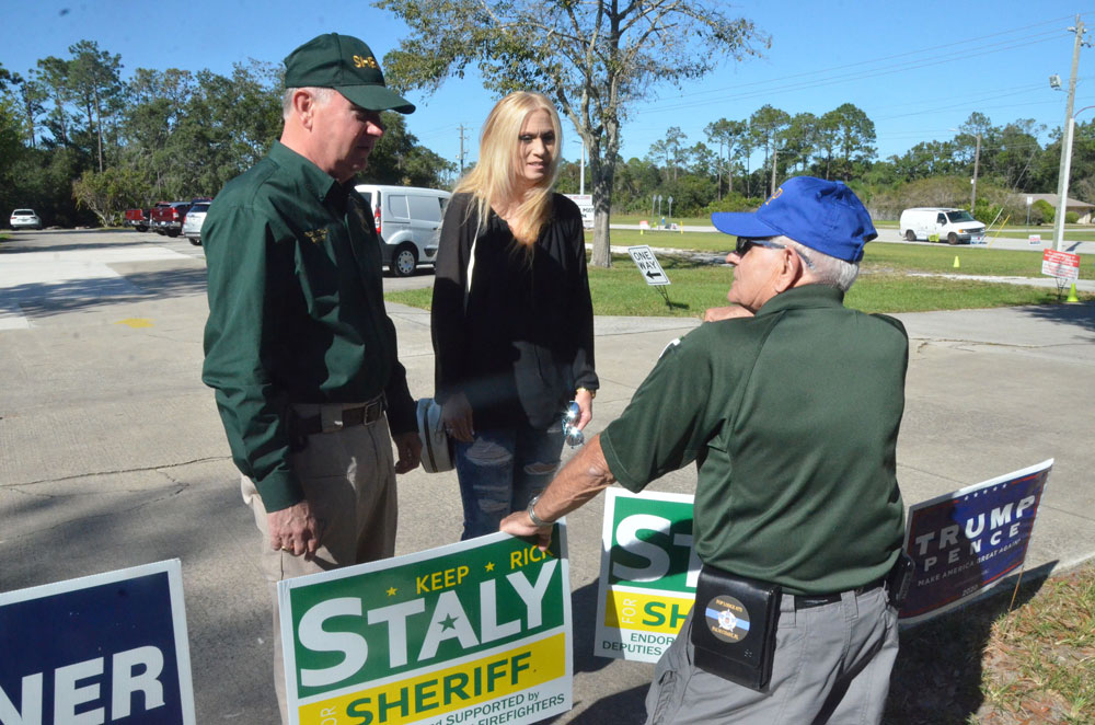 Rick and Debbie Staly talking to campaign volunteer John Caia in midafternoon today at the VFW precinct off Old Kings Road. Staly is an early winner in the election, easily winning his second term as sheriff. (© FlaglerLive)