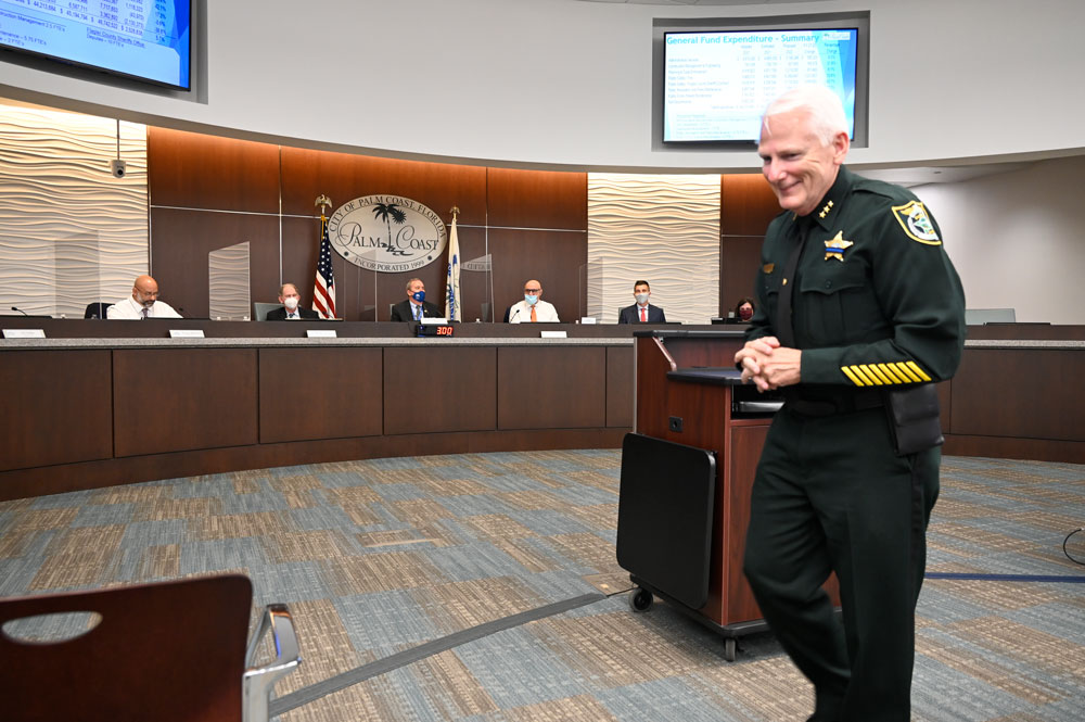 The Flagler County Sheriff's Office's Mark Strobridge had reasons to smile--10 reasons--as he walked away from the podium after answering questions from Palm Coast City Council members this evening. The council, with some disagreement, had granted the 10 additional deputies Sheriff Rick Staly requested. The council had a harder time settling on a property tax rate. (© FlaglerLive)