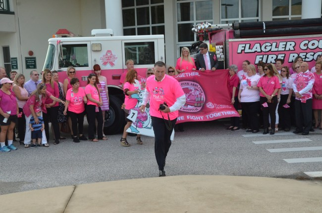 Always on the offensive, John Subers, center, is the commander in chief pof the Pink Army and the executive director of the Florida Hospital Flagler Foundation, which leads the annual fund-raising drive for Breast-Cancer Awareness Month. Subers this morning was getting set to take the picture of all those who'd gathered for the flag-raising in front of the Government Services Building just after 8 a.m.