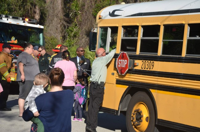 Transportation Director Andy West speaking to someone in the bus, with Earl Johnson, the superintendent's deputy, to West's left, moments before the children on the bus were  directed to another bus. Click on the image for larger view. (© FlaglerLive)