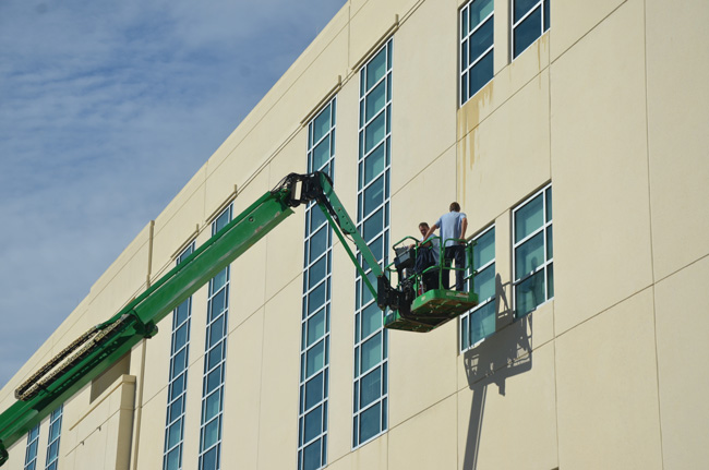 It takes a boom to keep those Flagler County courthouse windows clean: workers on Monday on the south facade of the building. (c FlaglerLive)