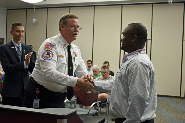 Palm Coast Fire Chief Mike Beadle, center, congratulates Brice Wright, a city utility employee, who was recognized with a proclamation Tuesday evening for helping victims of a vehicle crash in mid-June. Read the full proclamation here. (Cindi Lane)