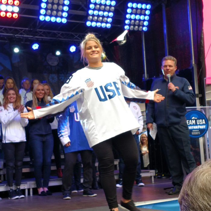 Team USA women's ice hockey member Brianna Decker models a Team USA ice hockey jersey at the 100 Days Out celebration in Times Square ahead of the PyeongChang 2018 Winter Olympics.