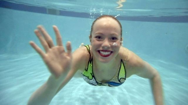 Olympic artistic swimmer Jacqueline Simoneau waves while being under water.