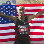 Marathon runner Abdi Abdirahman holds the American flag behind him after a race.