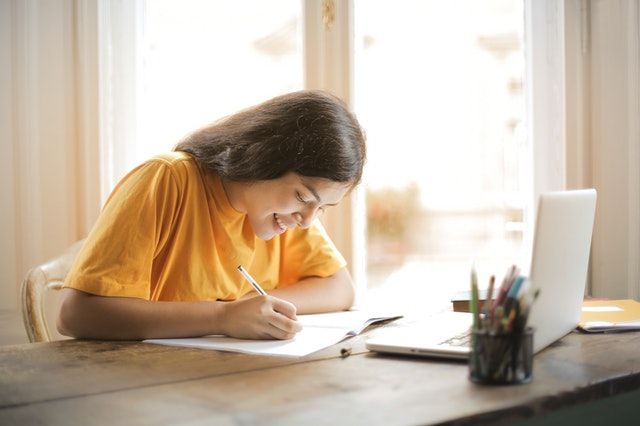 Woman writing on white paper in front of an open laptop