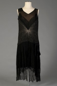 American, ca. 1927-1929. Black, metal beaded chiffon and black lace evening dress. Dress has a dropped waist, and starburst pattern of beads. It has a relatively high and uneven hem (shorter in the front than the back).
