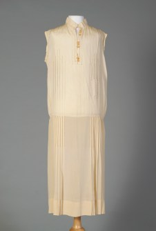 Probably American, ca. 1924-1928. Off-white silk chemise dress with pleated skirt, embroidered trim.