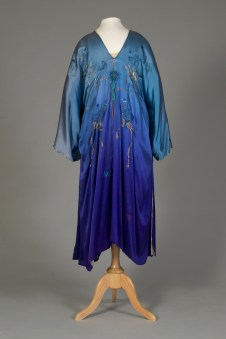 Probably American, ca. 1915-1925. Silk satin robe, light blue top shading to blue-purple at hem. Blue embroidered flowers with ribbons of couched gold thread.