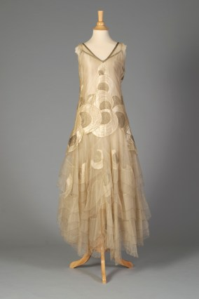 American, ca. 1928-1929. Cream net dress, sleeveless, gold embroidered trim, appliqued with cream and gold embroidery circle designs, graduated petal skirt layers edge with gold thread, attached charmeuse slip.