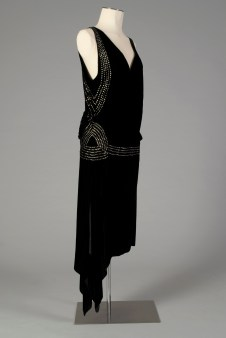 American, ca. 1920-1924. Black velvet with rhinestones. See the flounce at the hip as well as the decorated hip band. Also, the hemline is slightly longer than in later years.