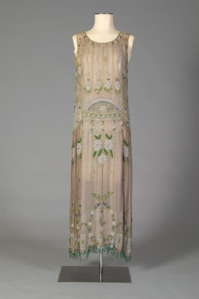 Probably American, ca. 1920-1929. Beige-grey finely pleated chiffon, heavily beaded in sunburst and floral designs.