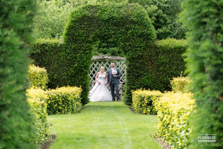 South East Wedding Gallery - Bride and Groom walking through hedged archway with groom holding the flowers