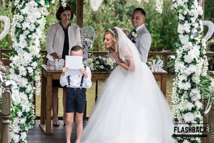 Child reading a speach with Bride watching over his shoulder